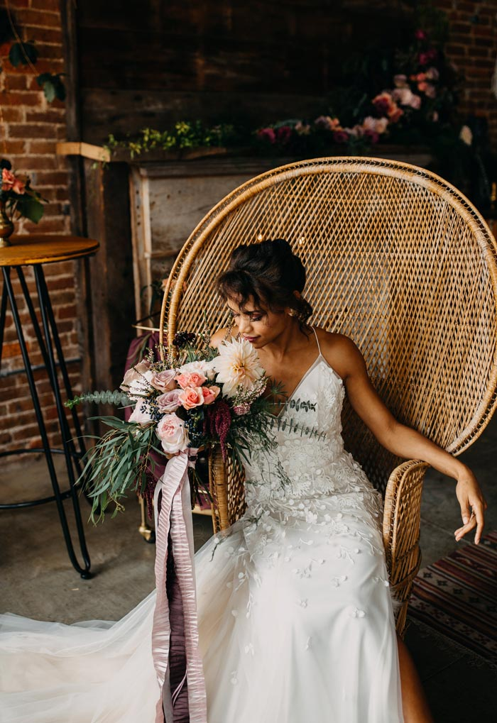 Bride sitting and holding a bohemian bridal bouquet