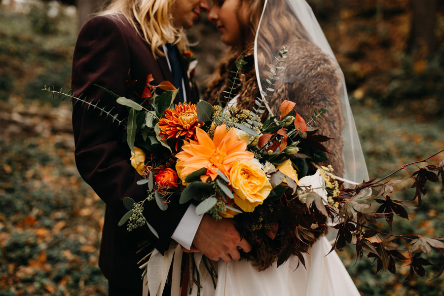 Couple holding orange and yellow fall-inspired bridal bouquet