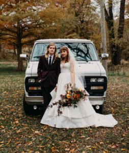 Couple standing in front of van on their wedding day