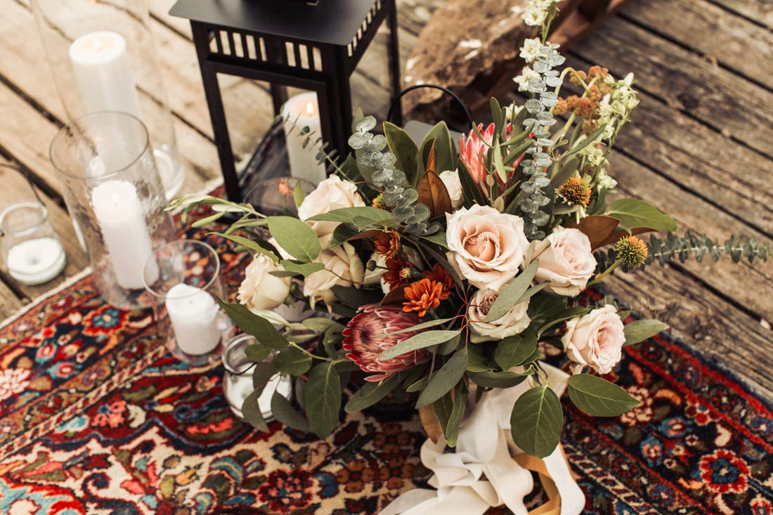 Bridal Bouquet with pink protea and pops of mustard laying on bohemian style rug
