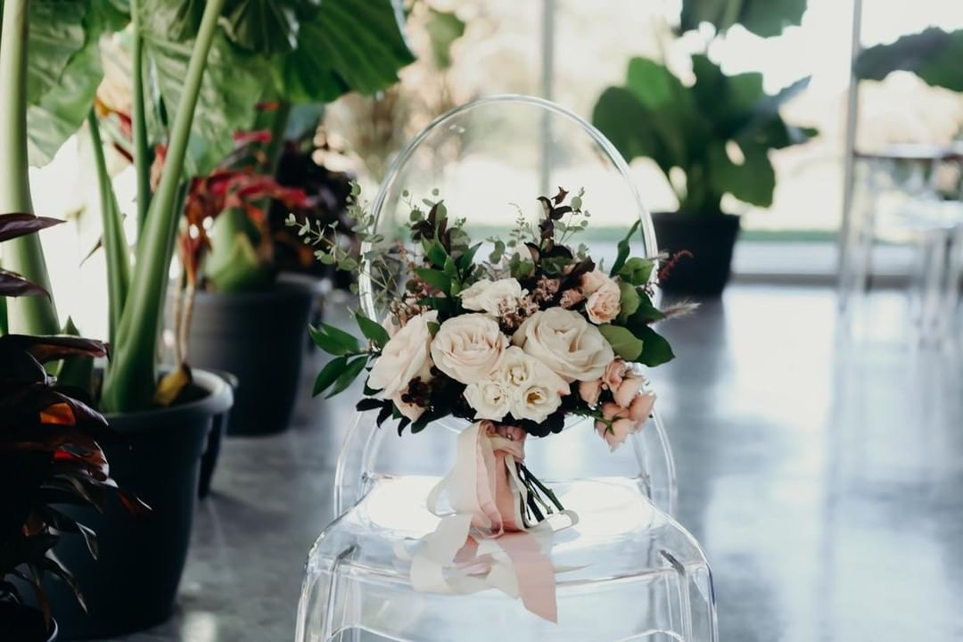 Bridal bouquet full of blush roses sitting on a clear acrylic chair