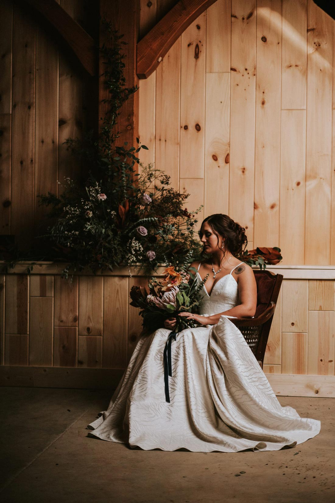 Bride seated in front of a floral installation with her bridal bouquet
