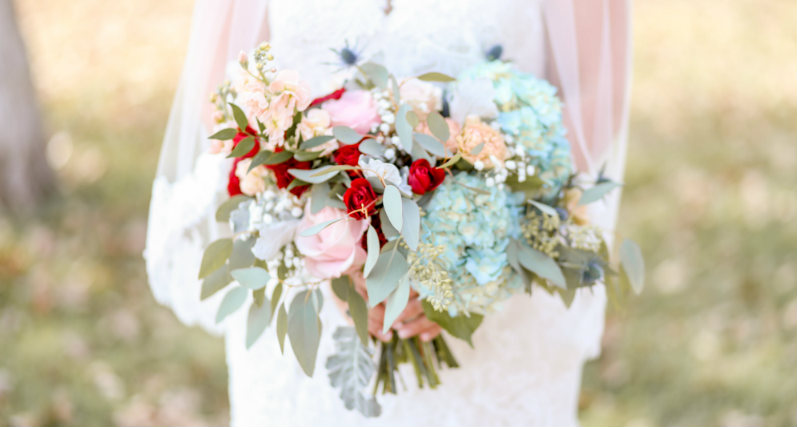 Bride holding her dusty blue, burgundy, and beige bridal bouquet