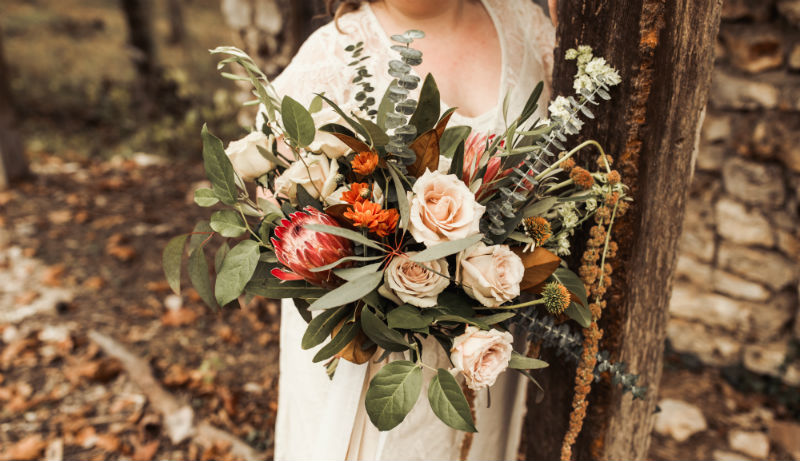 Bridal bouquet with protea, beige roses, and amaranth