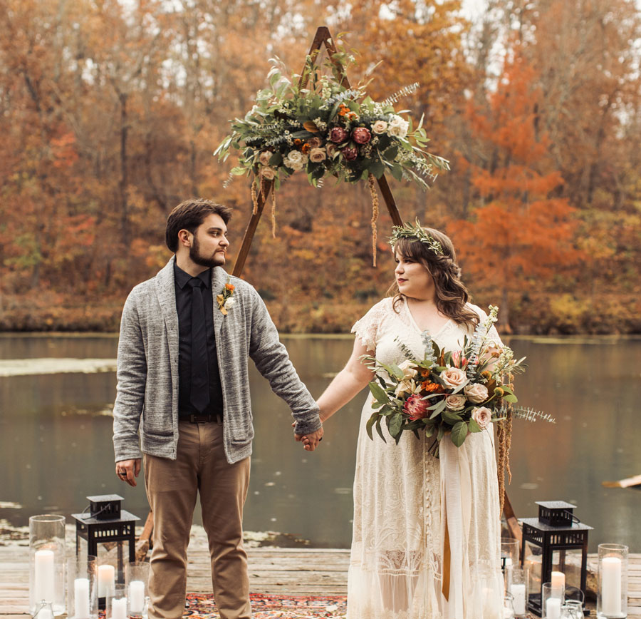 Couple standing in front of arbor for fall elopement