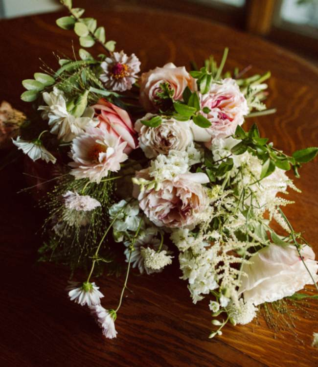 Blush and white bridal bouquet laying on table
