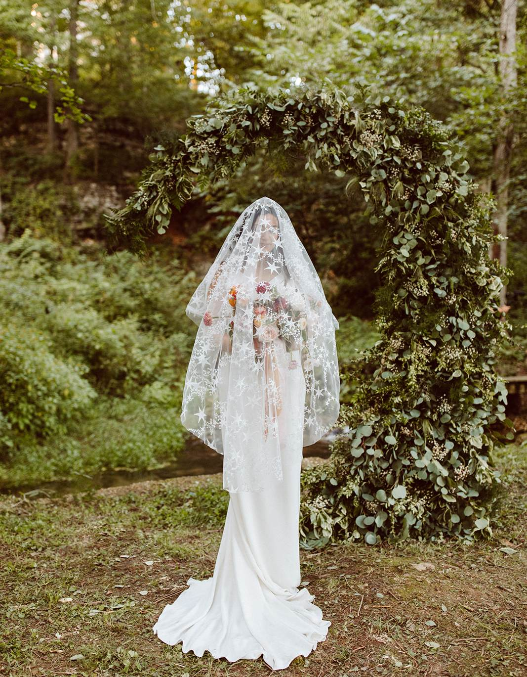 Veiled bride standing in front of a mystic moon installation