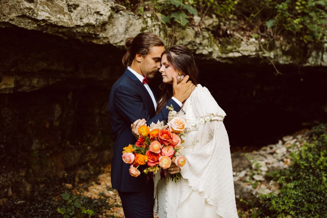 Bride and groom posing with bouquet in front of a cave