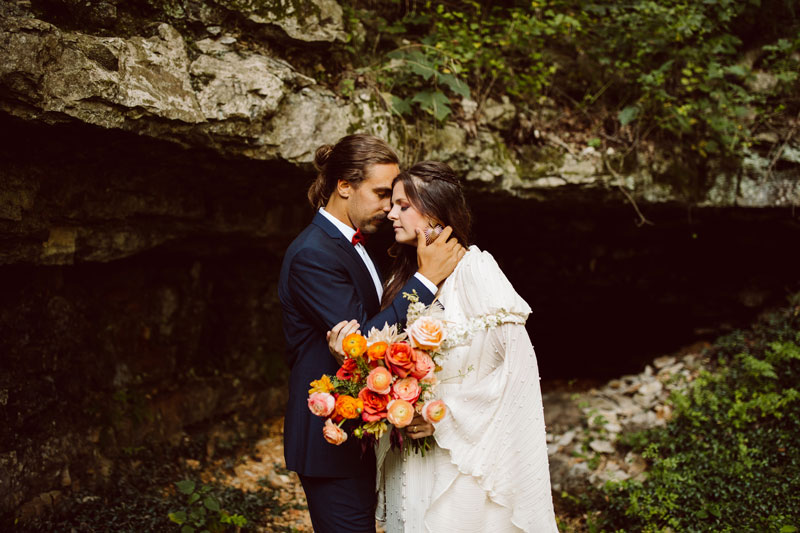 Couple standing in front of a cave
