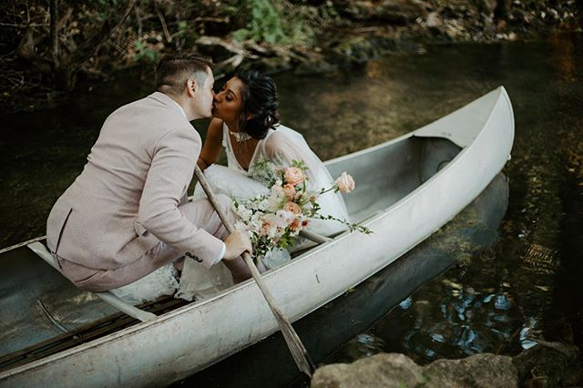 Couple kissing in canoe with bridal bouquet