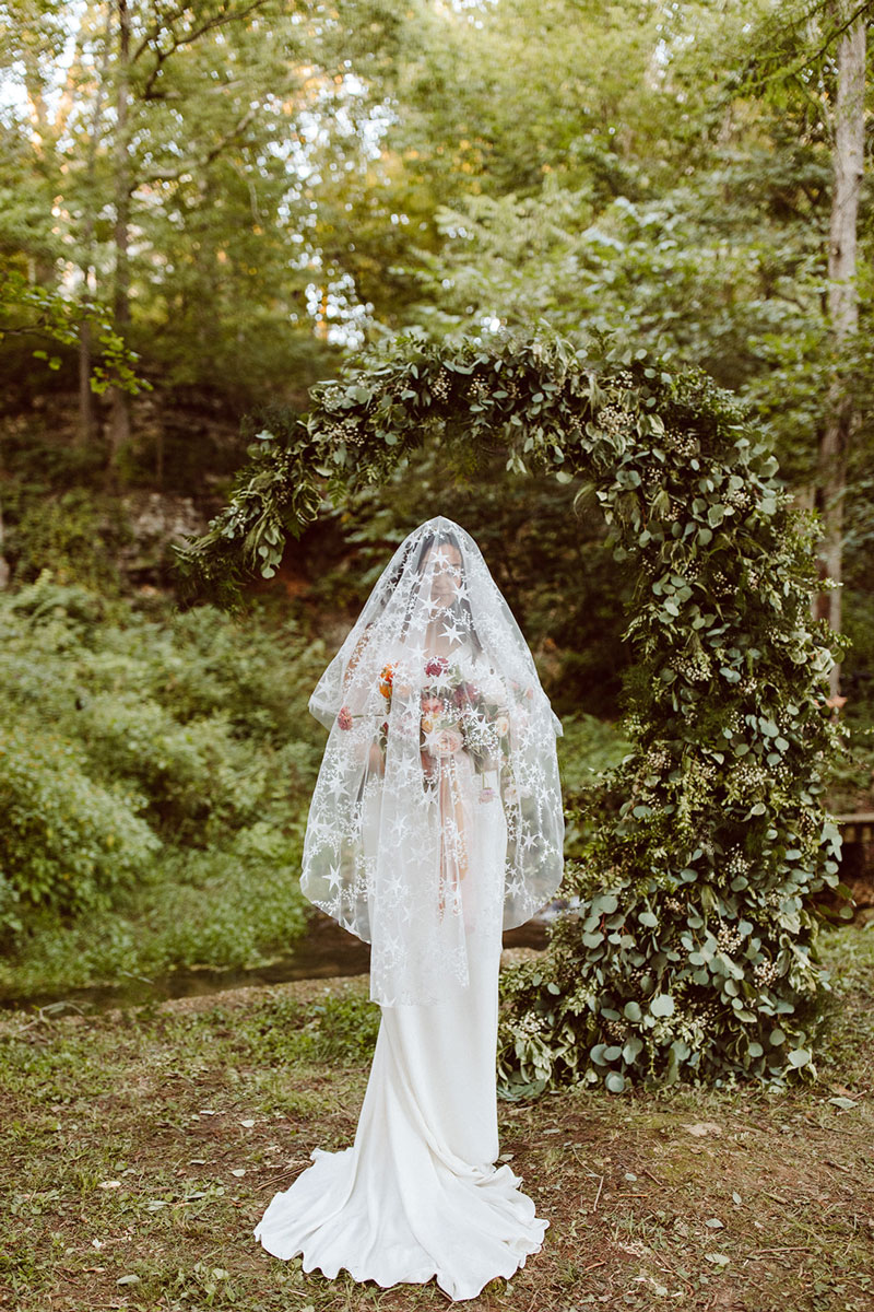 Veiled bride standing in front of greenery moon