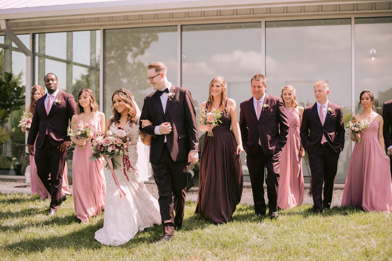 Wedding party posing outside of Greenhouse Two Rivers in monochromatic mauve suits and dresses