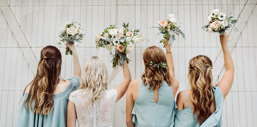 Bride and bridesmaids holding their bouquets above their heads