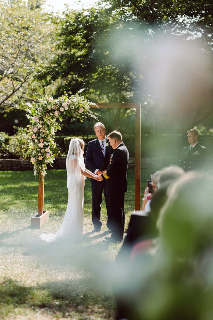 Couple getting married outdoor under a floral arbor