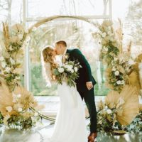 Couple kissing under dried floral installation