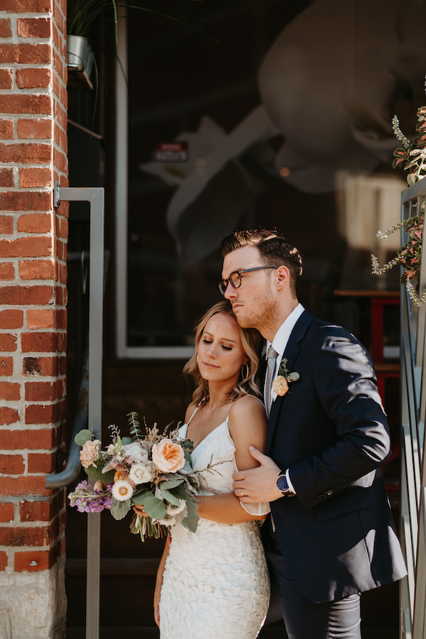 Couple standing outside with bridal bouquet