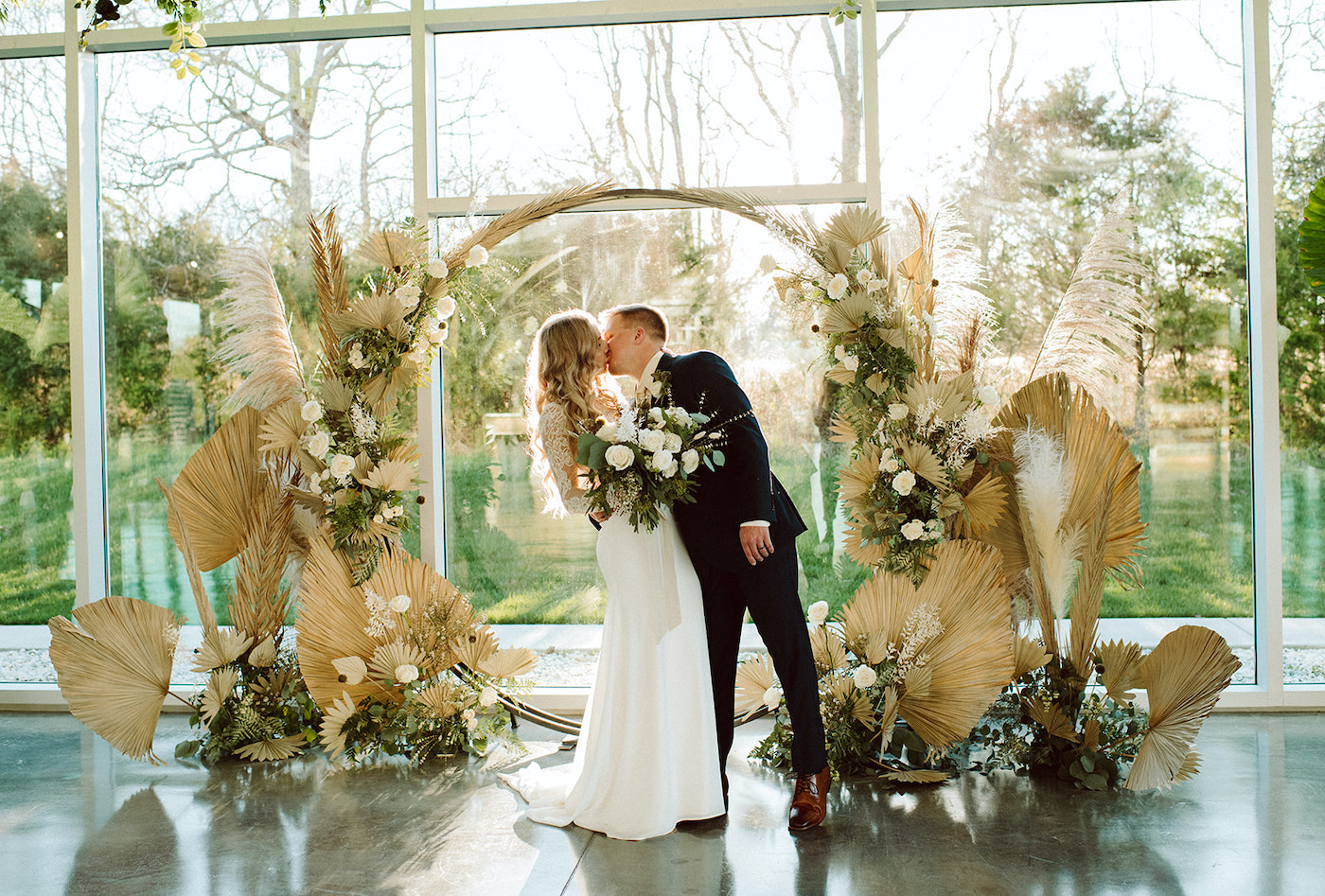 Couple kissing under dried floral arbor