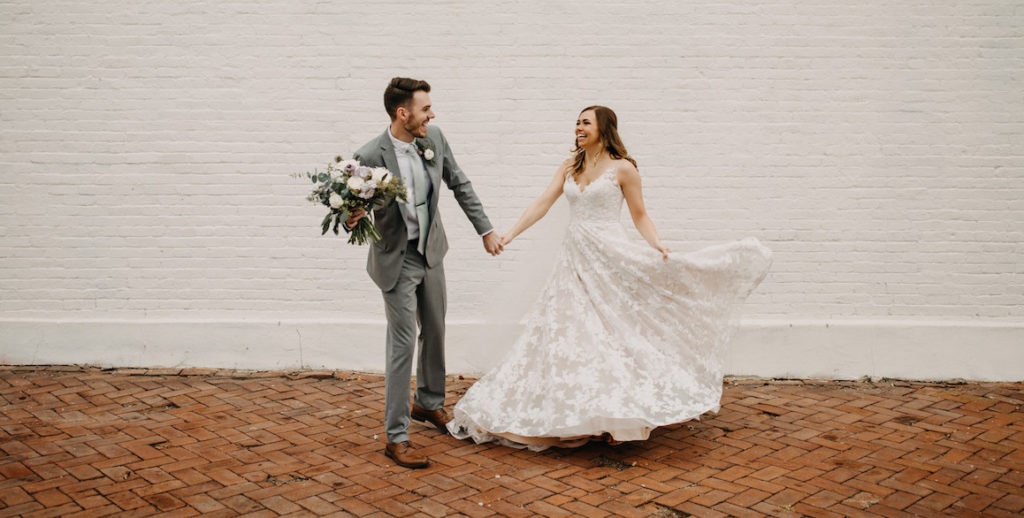 Groom holding bouquet while bride twirls her dress