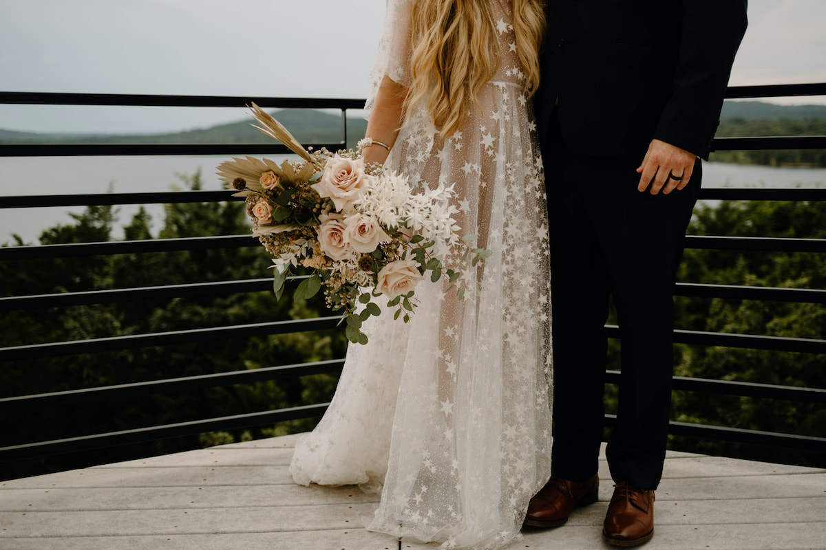 Bride and groom overlooking the lake with bridal bouquet