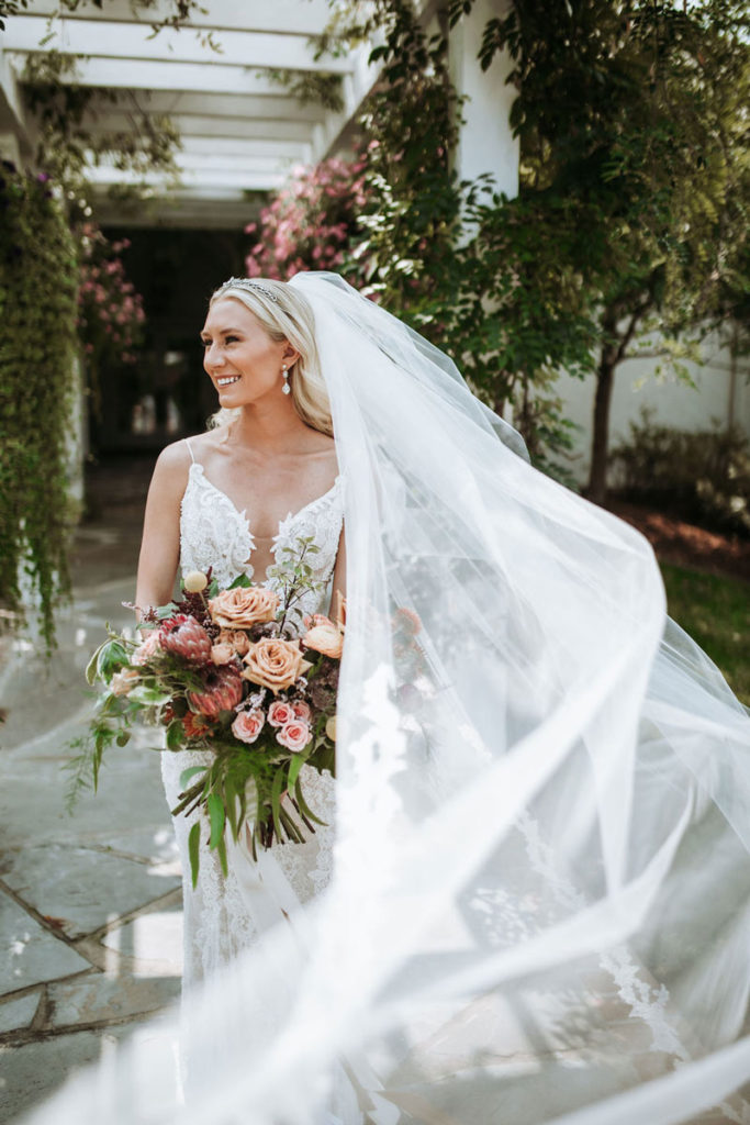 Bride holding bouquet and flowing veil