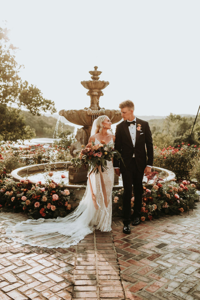 Bride and Groom standing in front of floral fountain