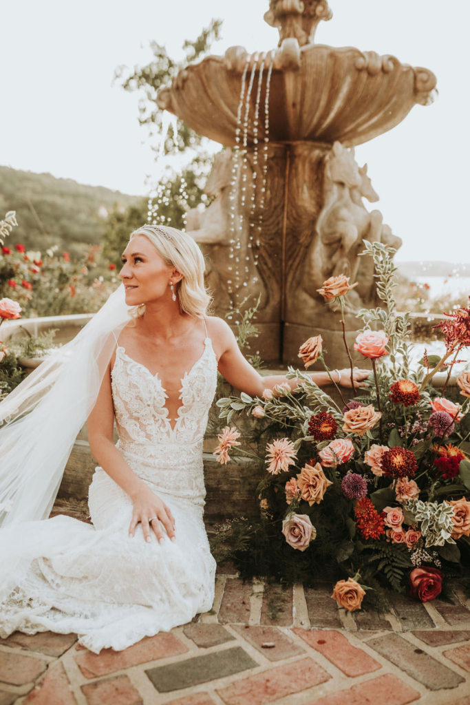 Bride sitting with fountain florals
