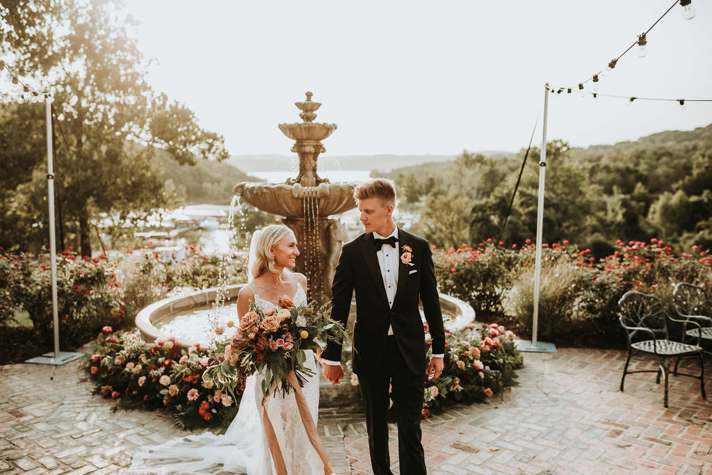 Bride and groom walking in front of floral fountain