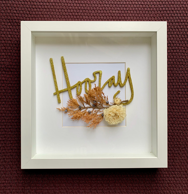 Shadow box with dried flowers and cake topper