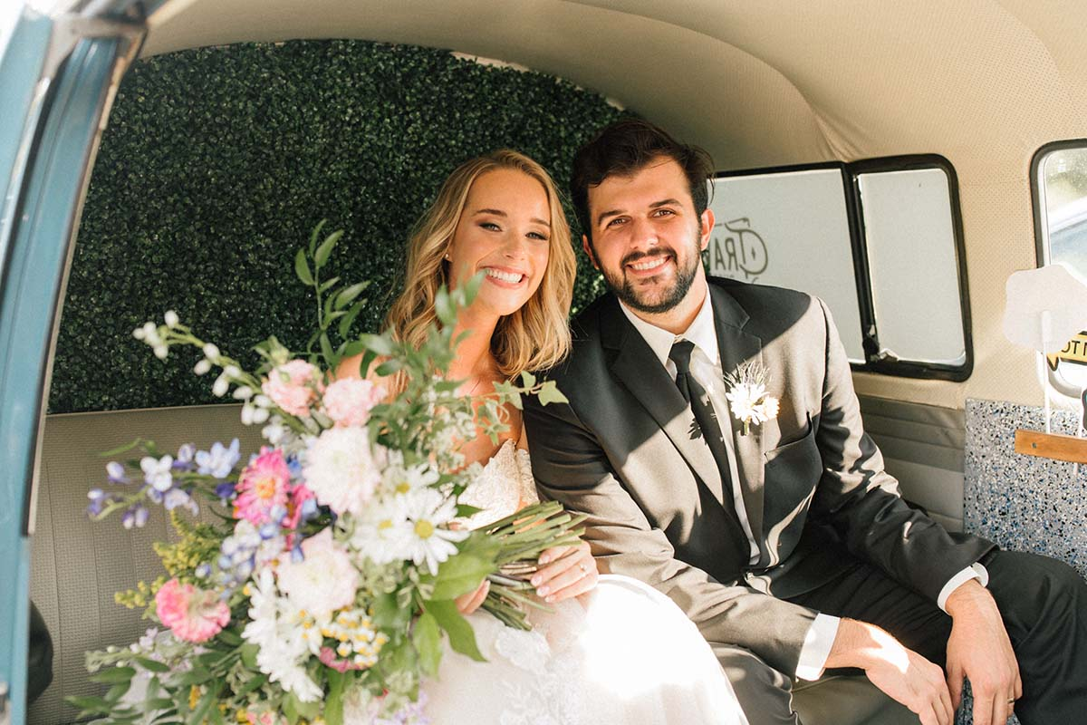 Newlyweds holding wildflower bouquet in photobooth van