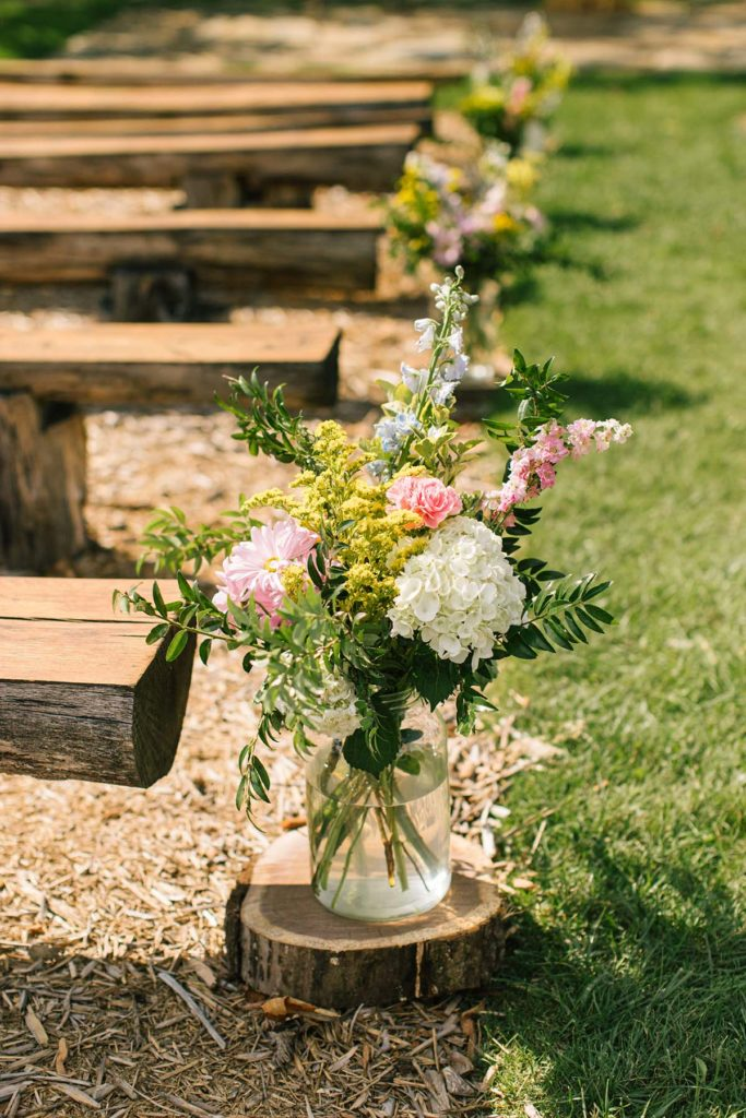 Wildflower arrangements lining the aisle