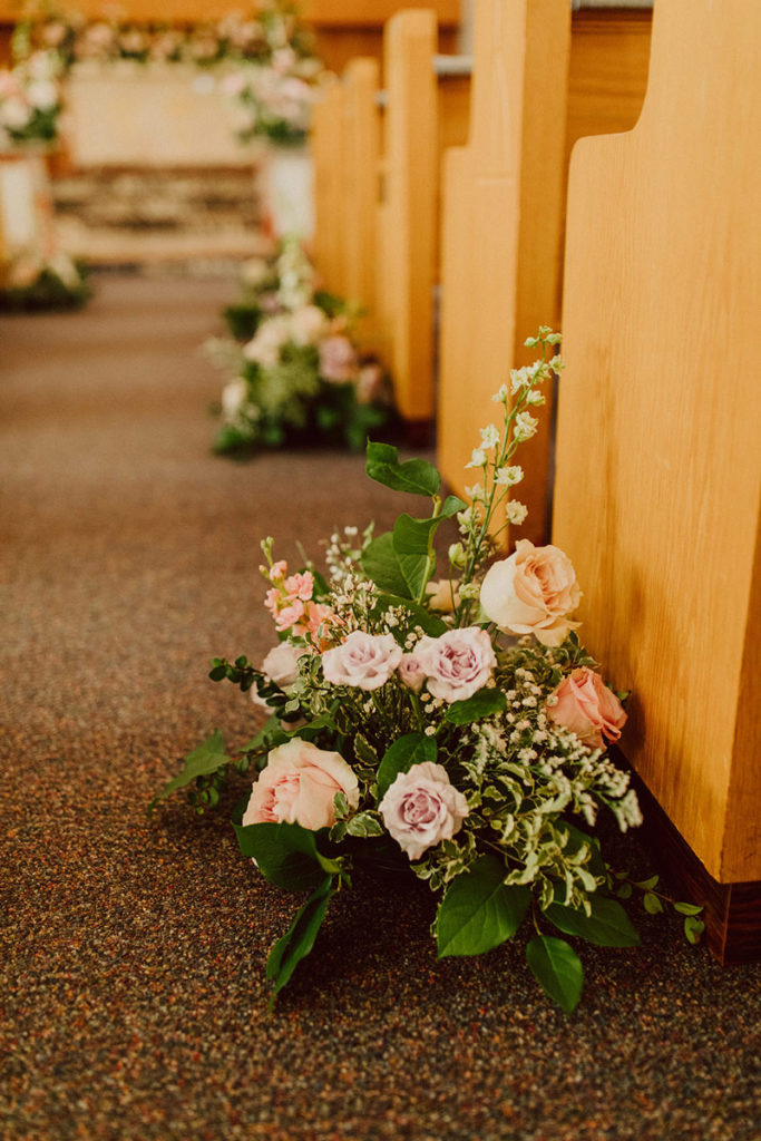 Florals at the base of chapel pews