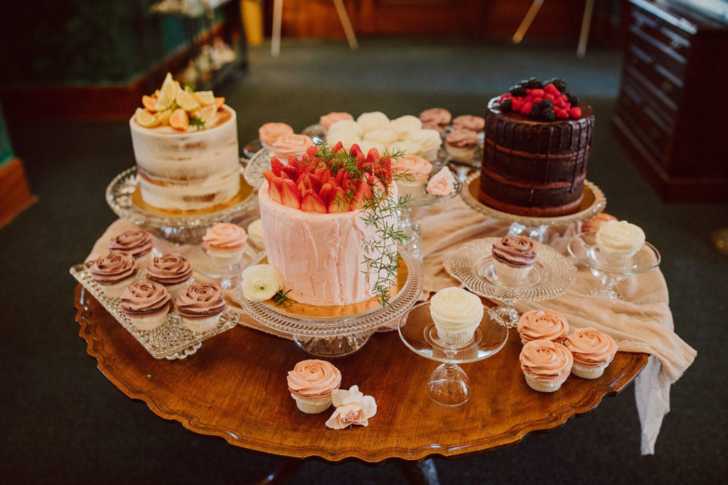 Round table full of berry-topped wedding cakes