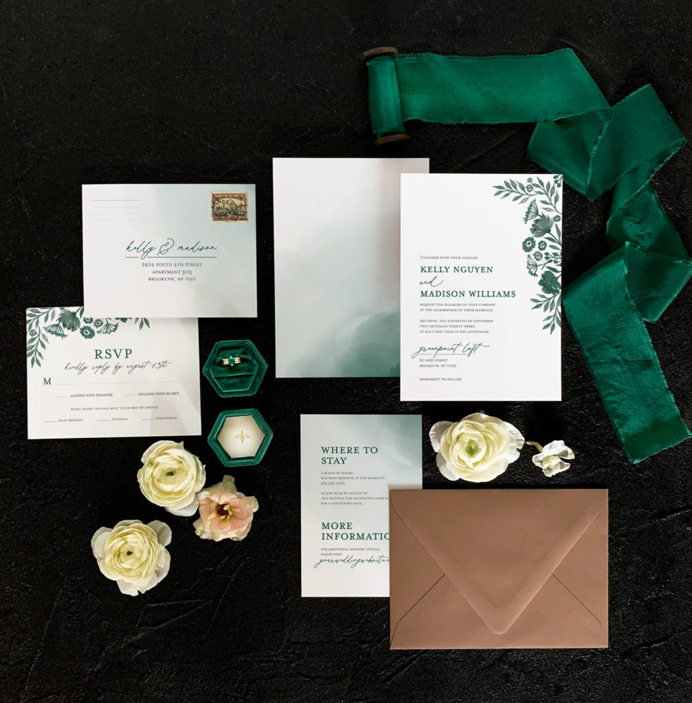Flat lay of the Daisy suite in emerald with emerald ribbon and a brown envelope