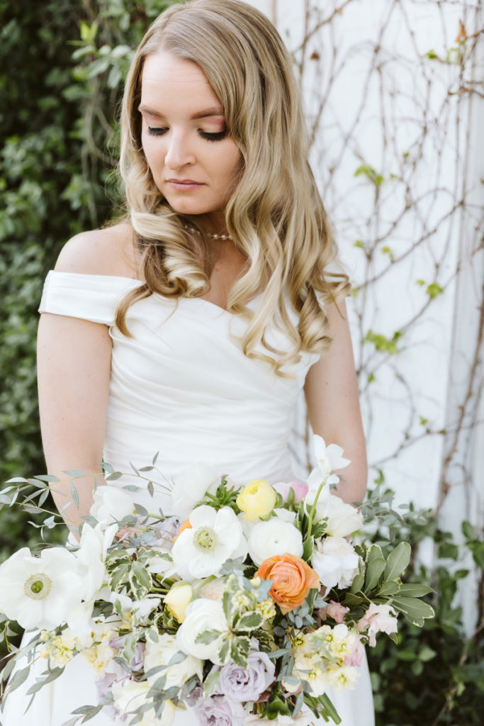 Bride holding pastel wedding bouquet including anemone, ranunculus, and orchids