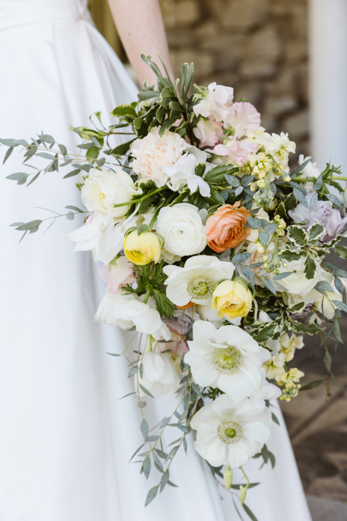 Close up of cascading bridal bouquet with white anemone and pastel ranunculus