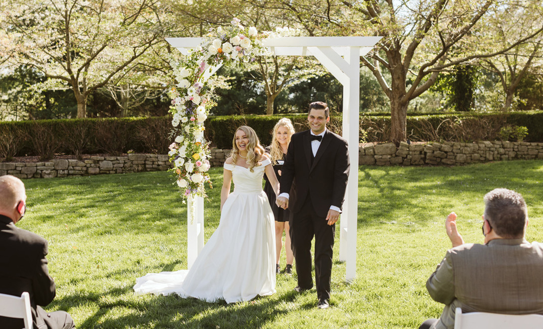 Bride and groom walking down the aisle with floral arbor in background