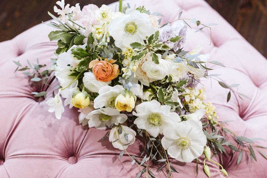 Spring bridal bouquet laying on tufted pink velvet ottoman