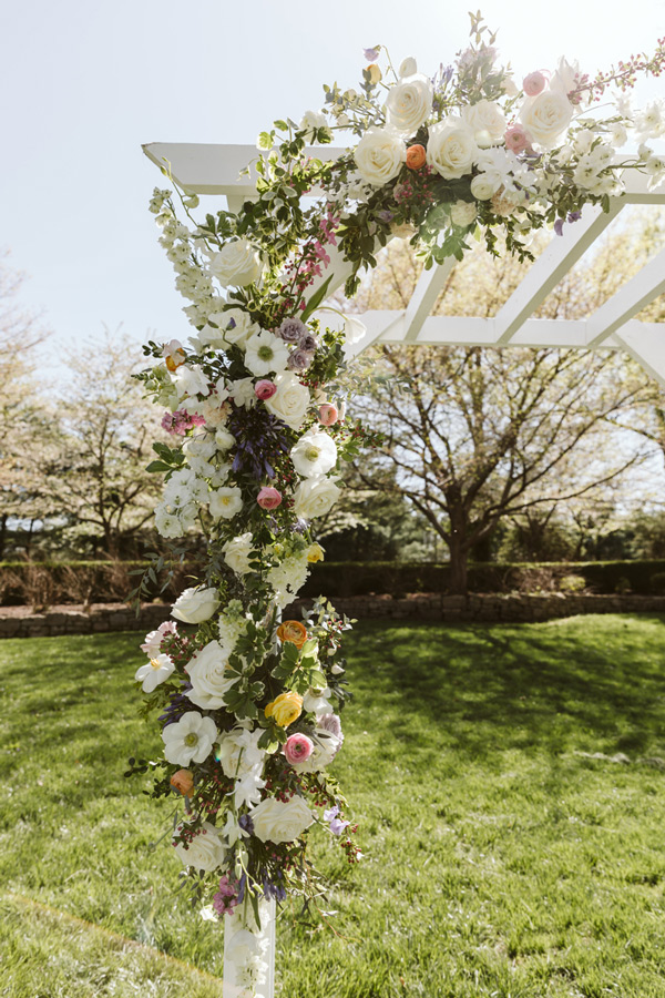 White floral Arbor adorned with spring flowers