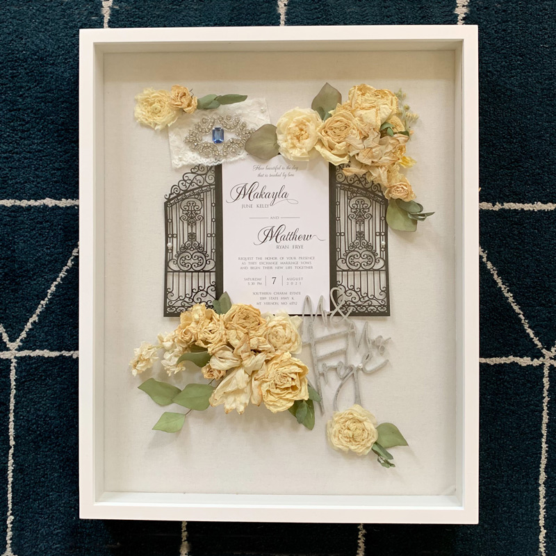 Memory box with dried flowers, wedding invitation, cake topper, and garter